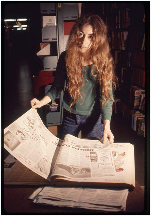Annastacia McDonald looks through newspapers at the Vancouver Public Library, 1976, Courtesy of Paul Wong